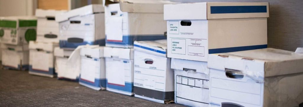 Boxes of files unorganized in store room