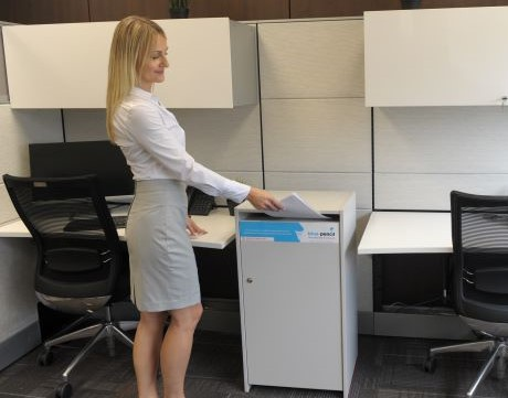 Person placing paper in office shredding console